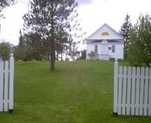 Front view of building with white fence and open portal; Town of St. George
