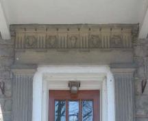 Fluted pilasters and decorated pediment displaying carved wreaths and a central lamb's head.; Lindsay Benjamin, 2007.