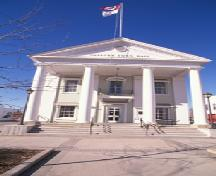 View of Napanee Town Hall, showing its two-storey, gable-roofed massing with a monumental pedimented portico with giant free-standing columns approached up broad steps, 1995.; Agence Parcs Canada / Parks Canada Agency, 1995.
