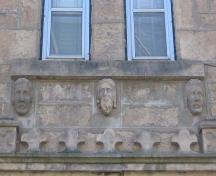 Detailed view of three of the carved stone heads found on the front (northeast) gable-end.; Lindsay Benjamin, 2007.