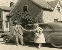 Couple posing with house in background, c. 1945; MacNaught Archives Acc. 063.1