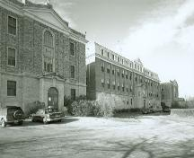 View of the Convent of Jesus and Mary, part of the Gravelbourg Ecclesiastical Buildings National Historic Site of Canada, showing its large brick façade and mansard roof with dormers.; Parks Canada Agency / Agence Parcs Canada