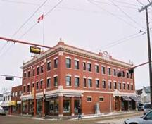 This image illustrates the overall form and massing of the Hull Block, in its prominent corner location. Also illustrated are the prominent name plaques in the arched pediments on the two prominent facades. (2004); City of Edmonton, 2004