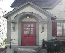 This photograph shows the elaborate entrance porch, the bracketed horse-shoe entablature and fanned wooden transom over the wood door with multi-paned glass panels, 2005; City of Saint John