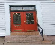 This image provides a view of the entry with the two paned transom window above paired doors, 2005; City of Saint John