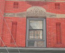 This photograph shows a window with an ornate sandstone lintel, 2005; City of Saint John