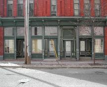 This photograph shows the storefront of the building and illustrates the recessed entranceways and cast iron pilasters, 2005; City of Saint John