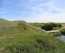 Archaeological remains were exposed in grassed-over road cut, left middle ground, 2004.; Government of Saskatchewan, Marvin Thomas, 2004.