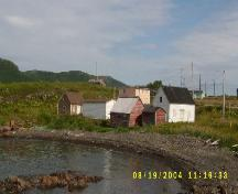 Photo view of William and Cecilia O'Neill Property from the oceanside, Conche, showing store, stable and house and environs, 2005; Joan Woodrow/HFNL 2008
