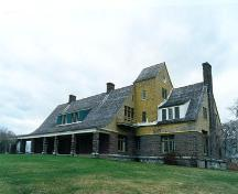 View of the façade of the Main House, showing Shingle styling and its roofline interrupted by a single dormer and deep front porch the length of the building's central core, 1995.; Parks canada Agency/ Agence Parcs Canada, L. Maitland, 1995.