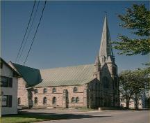 Corner view of St. Paul's United Church, showing the steeply pitched roofs and the corner tower with its tall spire, 1993.; Parks Canada Agency / Agency Parcs Canada, 1993.