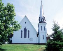 View of the exterior of Tryon United Church, showing its simple, bold form and composition, including its prominent, almost freestanding tower, and its massive, uninterrupted horizontal surfaces, 1995.; Parks Canada Agency / Agence Parcs Canada, J. Butterill, 1995.