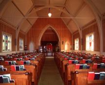 View of the interior of Tryon United Church, showing its interpretation of Gothic forms and detailing in wood, as seen in its faux-buttresses and its tripled Gothic arch stained glass windows, 1995.; Parks Canada Agency / Agence Parcs Canada, J. Butterill, 1995.