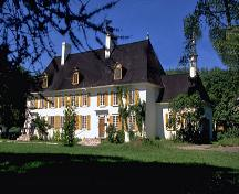 General view of Mauvide-Genest Manor, showing the nine-bay façade with regularly spaced wooden casement windows and two entry doors.; Parks Canada Agency / Agence Parcs Canada.