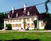 General view of Mauvide-Genest Manor, showing the substantial two-storey rectangular massing of the manor's main block under a steeply hipped roof broken by small dormer windows and two large chimneys.; Parks Canada Agency / Agence Parcs Canada.