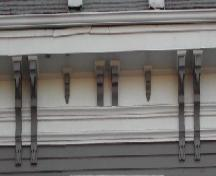 This image provides a view of the wood cornice supported by a series of paired and single brackets, 2006; City of Saint John