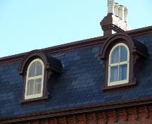 Detailed view of the bonnetted dormers located on the quadreplex, Devon Row, St. John's.  Note the original elaborate scrollwork.; Deborah O'Rielly/ HFNL 2007