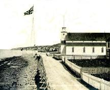Historic image of the original John Guy flagstaff. The present day flag and pole are located on the same site. Photo taken circa 1910.; Town of Cupids 2008