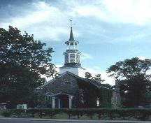View of the exterior of St. Stephen's Anglican Church, showing the three-tiered steeple and the main entrance with its double doors and semi-circular glass transom, 1992.; Parks Canada / Parcs Canada, 1992.