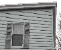 This photograph shows one of the upper storey windows and the eaves, 2005; City of Saint John