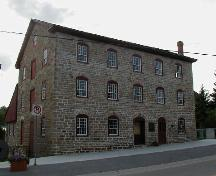 General view of the Old Stone Mill, showing its neo-classical, exterior detailing, including its bays trimmed with graceful, segmentally arched, stone voussoirs, 2004.; Parks Canada Agency / Agence Parcs Canada, 2004.