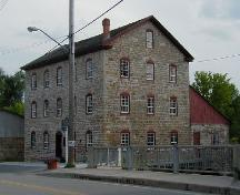 Corner view of the Old Stone Mill, showing its composition of five-bay façades with three-bay end elevations, 2004.; Parks Canada Agency / Agence Parcs Canada, 2004.