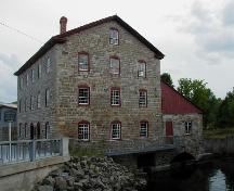Side view of the Old Stone Mill, showing its masonry construction with exterior walls of uneven coursed local stone with heavy stone corner quoins, 2004.; Parks Canada Agency / Agence Parcs Canada, 2004.
