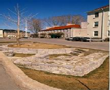 General view of Fort Frontenac, showing sections of the north curtain wall and the west curtain wall in a traffic circle at the intersection of Ontario Street and Place D'Armes, 1995.; Parks Canada Agency / Agence Parcs Canada, J. Butterill, 1995.