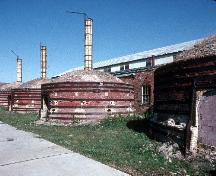 General view of Medalta Potteries, showing the beehive kilns with their brick exteriors, roof monitors, and roofing of wood shingles.; Parks Canada Agency / Agence Parcs Canada.