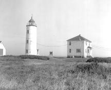 General view of Île-Verte Lighthouse, showing the spatial relationship of the lighthouse to the other buildings on the site, 1988.; Public Works / Travaux Publics, 1988.