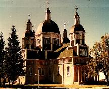General view of the Ukrainian Catholic Church of the Resurrection, showing the tight massing of its towers, many roof levels and four secondary domes around a large central dome, 1996.; Parks Canada Agency / Agence Parcs Canada, 1996.
