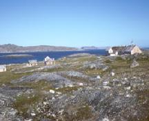 View of Hebron Mission in the distance, showing its isolated setting along the coast of Labrador, in proximity to the sea, 1994.; Parks Canada Agency / Agence Parcs Canada, I.K. MacNeil, 1994.