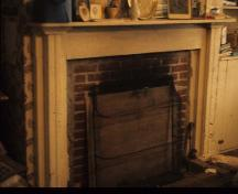Interior photograph of the Belmont House / R. Wilmot Home, showing gracefully tapered newel post and wood fireplace surrounds decorated with classically-inspired mouldings, 1975.; Canadian Inventory of Historic Buildings/ Inventaire des bâtiments historiques du Canada, ca.1975