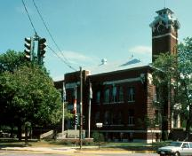 General view of Rivière-du-Loup Town Hall, showing the elements associated with town hall buildings, including its imposing central entry, square clock tower, and its brick facing material.; Parks Canada Agency / Agence Parcs Canada.