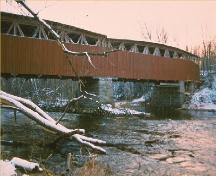 View of the exterior of Powerscourt Covered Bridge, showing the use of vertical wooden board and batten weatherboard siding.; Parks Canada Agency / Agence Parcs Canada.