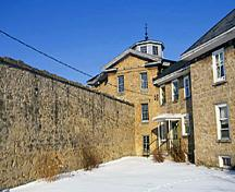Exterior view of the Huron County Gaol, showing the two-storey-high walls, 1995.; Parks Canada Agency / Agence Parcs Canada, J. Butterill, 1995.