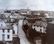 Historic view up Church Street with Christ Church Churchyard Cemetery at corner lot at centre right, with former Christ Church building on its grounds, Bonavista, NL, circa early 1900s; Orville Harris - Bona Photo Media Gallery, Town of Bonavista web site: www.bonavista.net