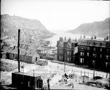 Historic photo of Devon House (near middle) taken pre-1892 fire; view at background of the photo shows the St. John's Narrows and Signal Hill.; Government of Canada Collections 2006