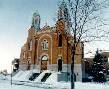 General view of St. George Antiochian Orthodox Church, showing the symmetrical façade, central dome and paired towers with cupolas.; Parks Canada Agency / Agence Parcs Canada.