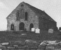 Historic photo view facing front of former Roman Catholic stone church with cemetery, looking west, Torbay, NL, circa 1900; Torbay Museum, 2006