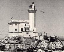 General view of Triple Island Lighthouse, showing the clean lines, and subtle ornamentation, including the decorative brackets supporting the platform surmounted by an iron lantern.; Parks Canada Agency / Agence Parcs Canada.