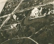 Aerial view of the Temple of the Church of Jesus Christ of Latter Day Saints, showings its siting in the midst of a landscaped square with a surrounding stone wall separating it from the surrounding town, 1926.; Department of Energy, Mines and Resources / Ministère de l'Énergie, des Mines et des Ressources, 1926.