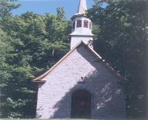 View of the main entrance to Sainte Anne Processional Chapel, showing its compact single storey massing under a steeply pitched gable roof with bellcast eaves, 1999.; Parks Canada Agency / Agence Parcs Canada, 1999.