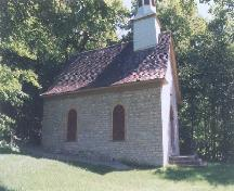 View of the façade of Sainte Anne Processional Chapel, showing its solid rubblestone walls and wood shingle roofing, 1999.; Parks Canada Agency / Agence Parcs Canada, 1999.