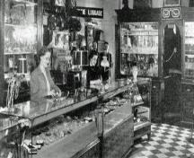 Interior view of Moss Jewellers, Amherst, NS, ca. 1949. Leon Moss can be seen in the background, one of two men standing under the luggage sign.; Courtesy of the Town of Amherst