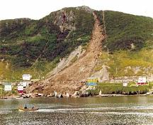 Picture showing the destruction caused by the landslide of August 1973. The remains of houses destroyed by the landslide can be seen at the water's edge.; Government of Newfoundland and Labrador 1973/ HFNL 2009