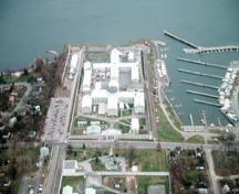 Aerial view of Kingston Penitentiary, showing the Greek cross (Auburn style) footprint of the original cellblock with its four three-storey wings, 1991.; Parks Canada Agency / Agence Parcs Canada, J.P. Jérôme, 1991.