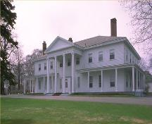 Corner view of the Government House in Charlottetown, showing the single-storey verandah, and its symmetrically organized elevations with evenly spaced multi-pane sash windows, 1989.; Parks Canada Agency / Agence Parcs Canada, 1989.
