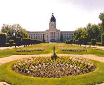 General view of the Legislative Building, showing its lawns, flower beds, shrubs and trees encircled and crossed by walkways and driveways, 1998.; Parks Canada Agency / Agence Parcs Canada, 1998.