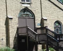 Of note is the gothic window above the door that displays the Church's name.; Kendra Green, 2007.